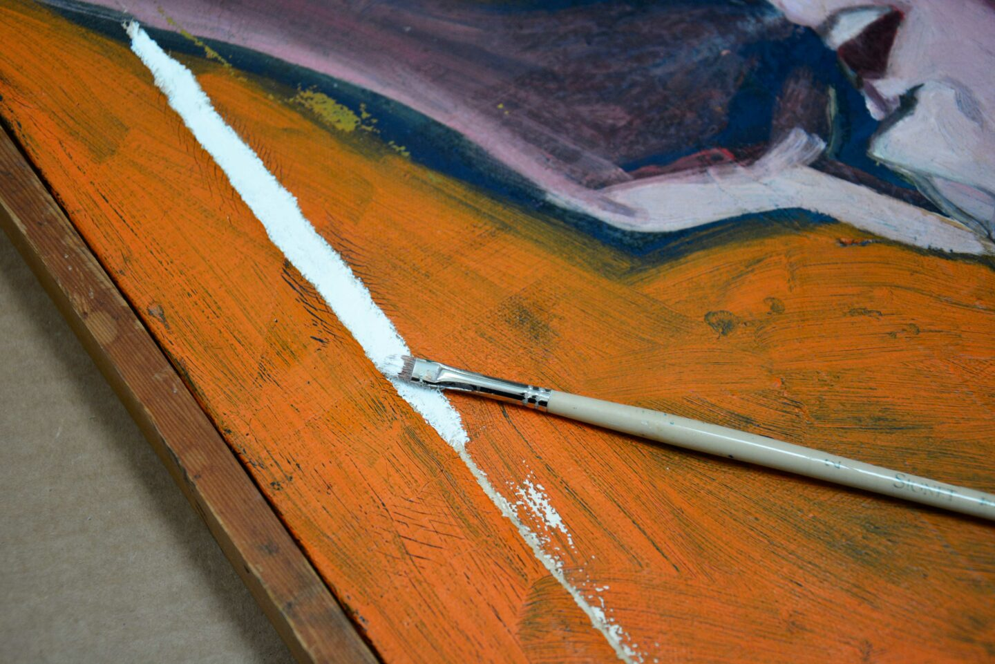Using gesso to fill in a tear in damaged art.