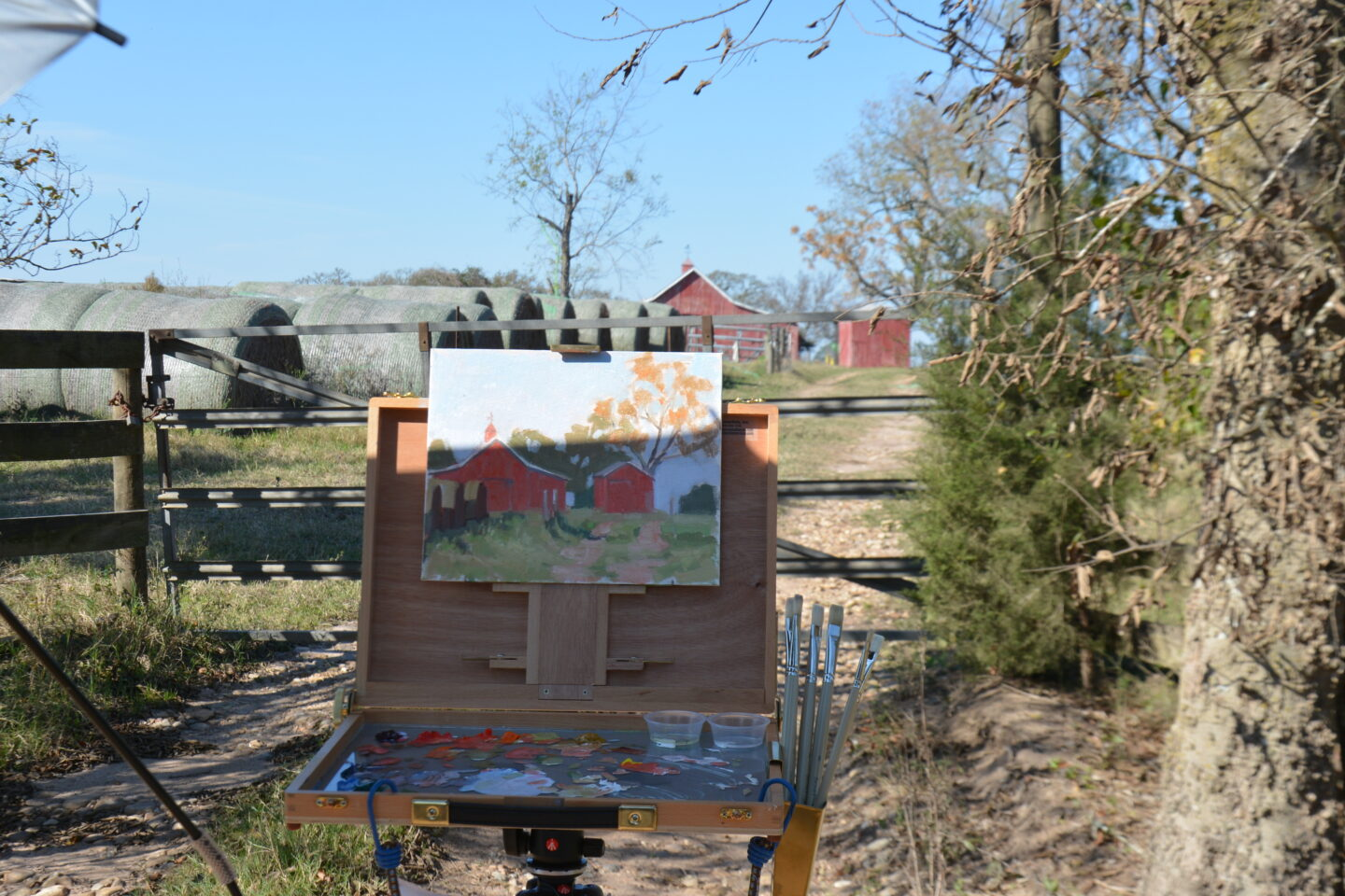 Plein air painting a red barn.